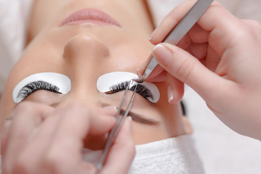 67606949 - permanent makeup. eyelash extension procedure. woman eye with long eyelashes. professional stylist lengthening female lashes. eyelash extension procedure - master and a client in a beauty salon
